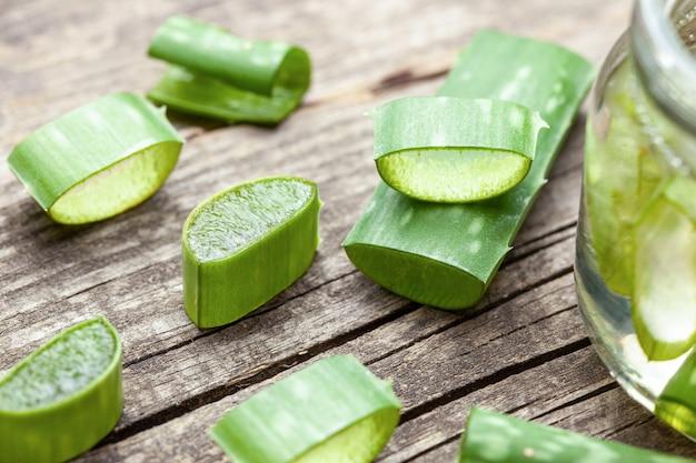 Aloe vera gelcreme für die haut- und körperpflege. aloe-fruchtfleischscheiben in einem glas und blätter auf einem holztisch. kosmetische lotion.