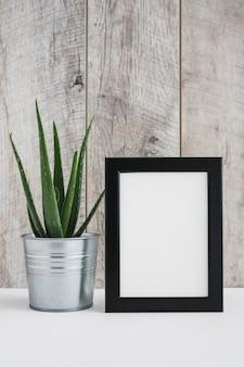 Aloe vera im aluminiumbehälter mit weißem bilderrahmen gegen holzwand