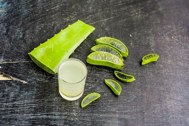 Aloe vera stücke und aloe gel im glas auf einem alten dunklen holzhintergrund