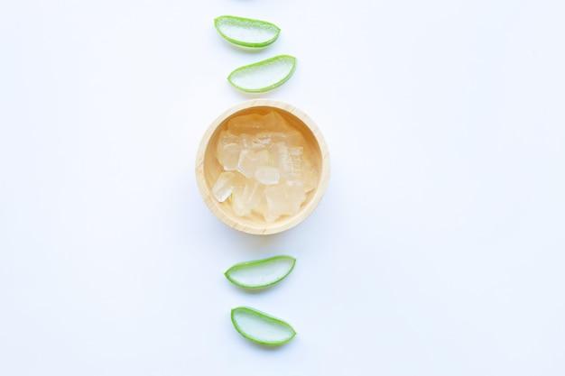 Aloevera-scheiben mit aloevera-gel in der hölzernen schüssel auf weiß