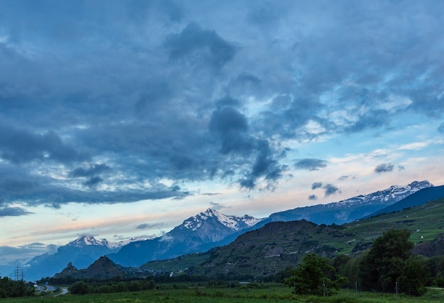 Alpenbergsommermorgenansicht mit burgen tourbillon und montorge und schneebedeckten felsspitzen in der ferne, sion, schweiz