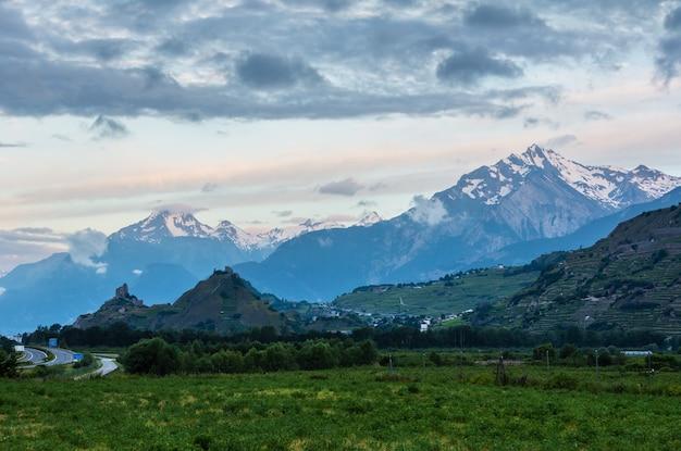Alpengebirgs-sommermorgenansicht mit schlössern tourbillon und montorge und schneebedeckten felsgipfeln im fernen sion, schweiz.