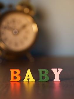 Alphabet baby auf holztisch und vintage wecker