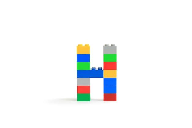 Alphabet buchstaben h aus bunten kunststoff-brick block konstruktor isoliert auf weißem hintergrund