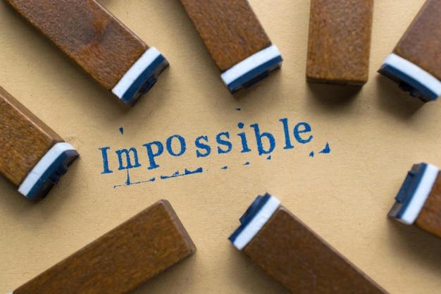 Alphabetbuchstabenwort unmöglich vom stempelbuchstabenguß auf papier für unmöglichen hintergrund