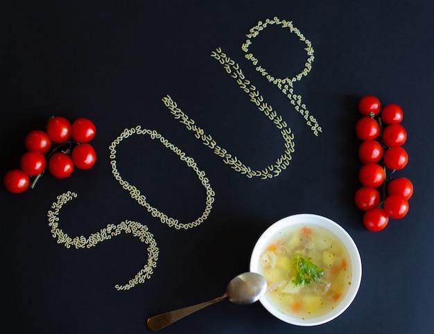 Alphabetsuppe in einer weißen platte mit kirschtomaten und der aufschrift der buchstabeteigwaren