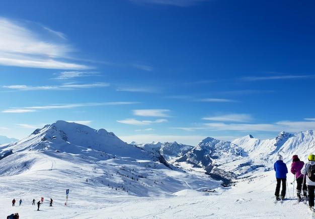 Alpiner schneebedeckter berg und skifahrer
