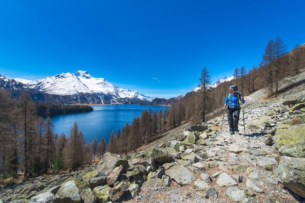 Alpines trekking auf den schweizer alpen ein mädchen, das mit einem großen see wandert