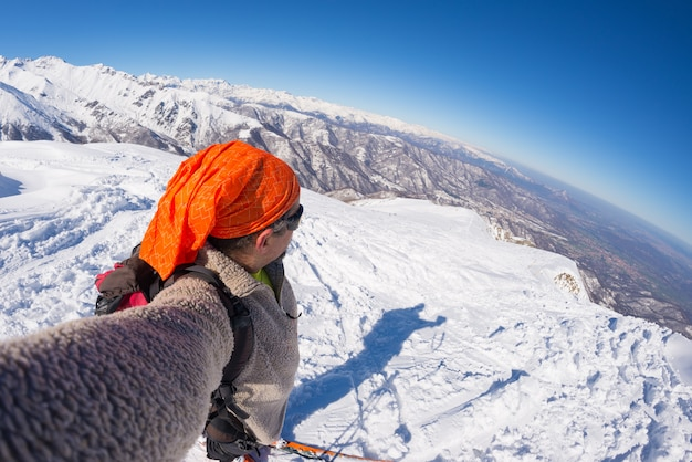 Alpinist, der selfie auf schneebedecktem berg nimmt