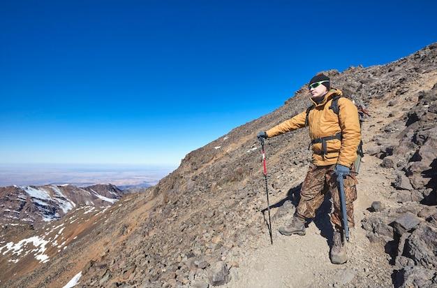 Alpinist im hochatlasgebirge. kaukasische männer in der sonnenbrille auf einem berghang mit alpenstock, eispickel und touristenrucksack. winterpanoramaansicht. reisefotografie.