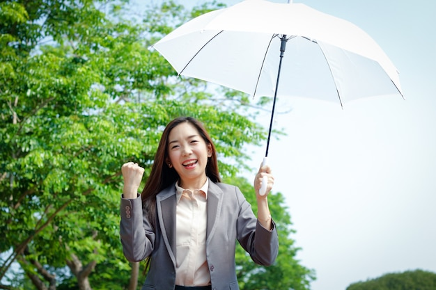 Als geschäftsfrau im anzug hält sie einen sonnenbeschatteten weißen regenschirm in der hand