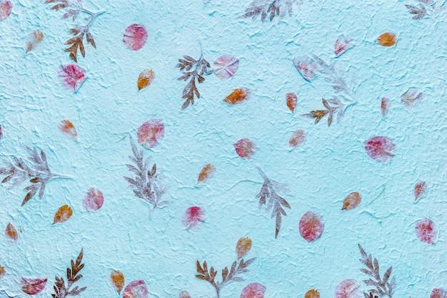 Als hintergrund wird blaues maulbeerpapier mit der textur von blumen und laub verwendet.