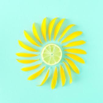 Als inspiration für die sonne auf blauem grund eine scheibe zitronenfrucht und sonnenblumenblüten um ihn herum angeordnet. sommer sonniges konzept von hellen farben.