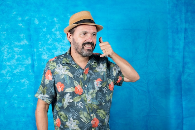 Als tourist verkleidete person mit bedrucktem hemd und mit der hand auf dem gesicht, als ob er am telefon wäre