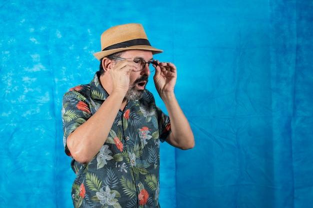 Als tourist verkleideter mensch mit bedrucktem hemd und erstauntem gesicht, der seine brille abnimmt