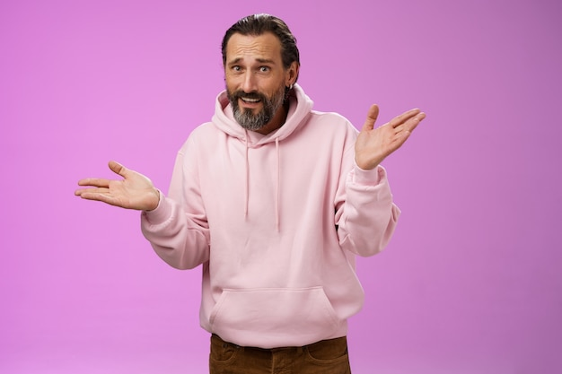 Also, was beißt mich? porträt unwissend sorglos cool stilvoll reifen bärtigen mann ohrring rosa hoodie achselzucken hände seitwärts verspotten sein unhöflich stehen sauer sauer nicht bereit zu stehen lila hintergrund.