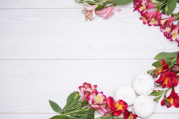 Alstroemeria blüht hintergrund mit weißem zephir auf weißem hölzernem hintergrund.