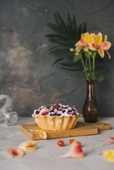 Alstroemeriablumenvase nahe dem geschmackvollen beerentörtchen auf hackendem brett