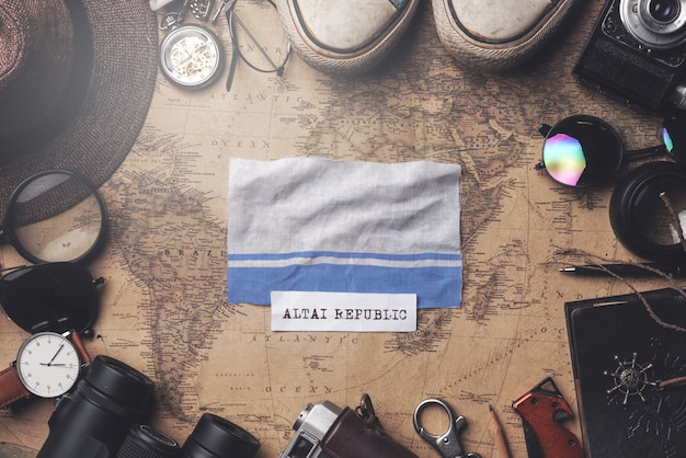 Altai-republik-flagge zwischen dem zubehör des reisenden auf alter weinlese-karte. obenliegender schuss