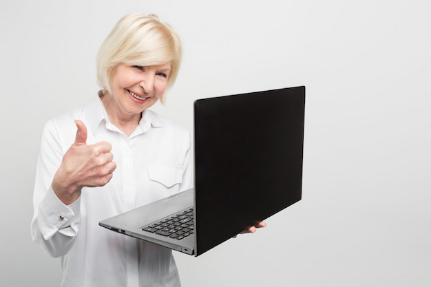 Alte aber moderne frau hält einen neuen laptop. sie benutzt es gerne. die dame möchte lieber alles über neue technologien und die letzten neuigkeiten über computerausrüstung wissen.
