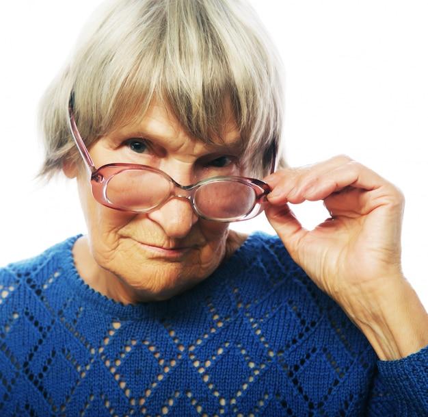 Alte ältere dame, die durch ihre brillen schaut