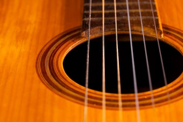 Alte akustikgitarre an einer schwarzen wand.