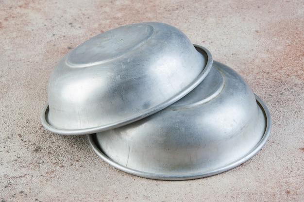 Alte aluminiumschalen auf betonhintergrund