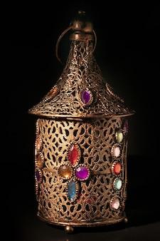 Alte arabische bronze-lampe lokalisiert auf schwarzer oberfläche