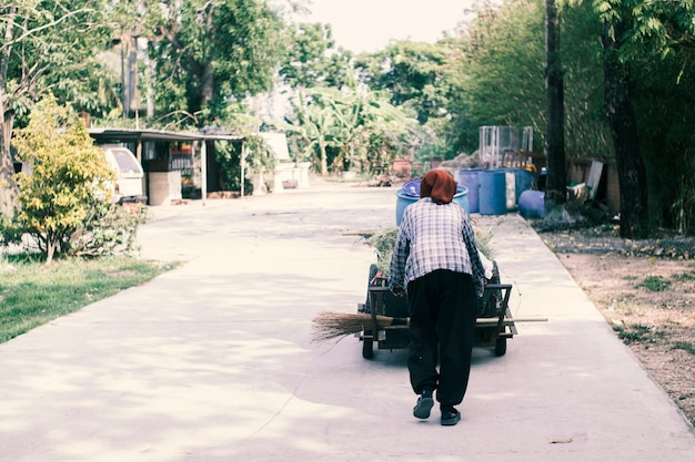 Alte arme asiatische frau mit einem müllwagen