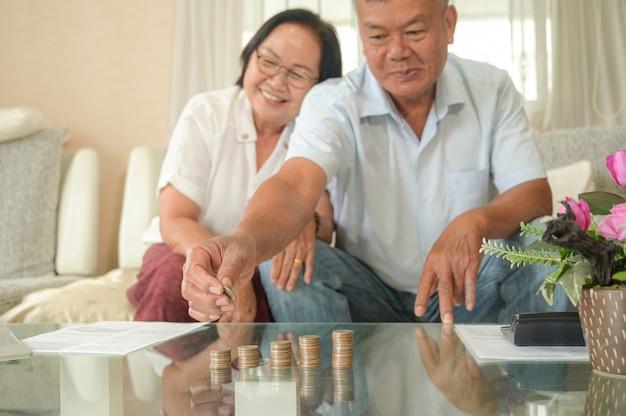 Alte asiatische frauen und männer sitzen auf dem sofa, sie machen finanzielle pläne.
