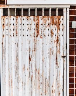 Alte ausführliche gealterte rostige braune strukturierte stahllegierungstürausdehnung der ladenfront