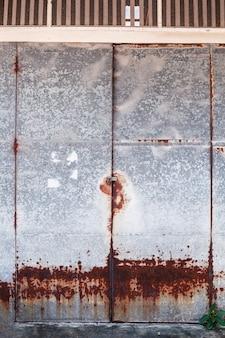 Alte ausführliche gealterte rostige rote braune strukturierte zinklegierungsblech-außenzaunklappe