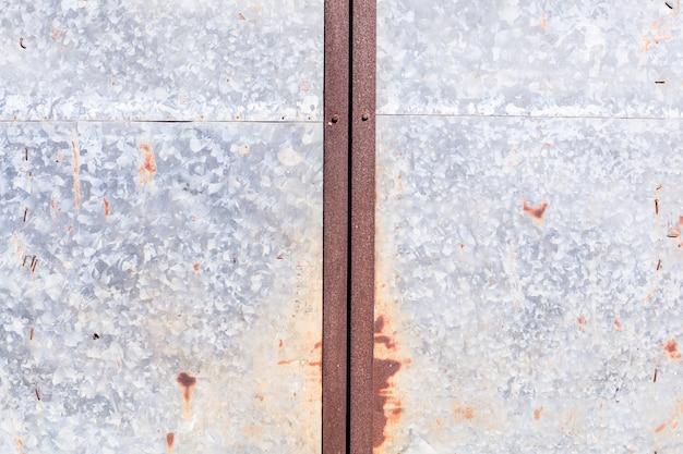 Alte ausführliche gealterte rostige rote braune strukturierte zinklegierungsblechtafel-zauntür des lagers