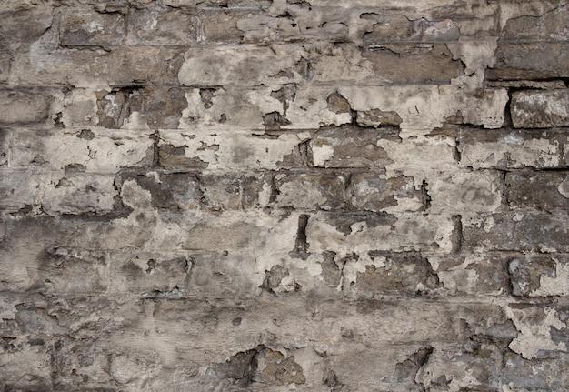 Alte backsteinmauer mit abblätternder farbe, sepia-farbe, strukturiertem hintergrund