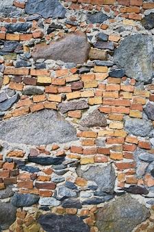 Alte backsteinmauer mit kopfsteinpflaster, grunge-hintergrund. kopieren sie platz für text. vertikal