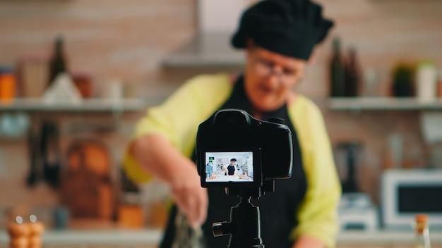 Alte bäckerin, die essensrezept zum kochen von podcasts aus der küche präsentiert. pensionierter blogger-koch-influencer, der internet-technologie verwendet, kommuniziert und blogging in sozialen medien mit digitaler ausrüstung fotografiert