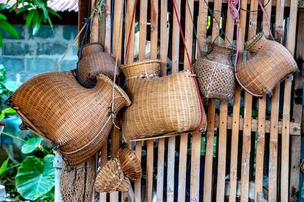 Alte bambusfischfalle oder -weisselchen, die an der wand des hauses in ländlichem, thailand hängt.