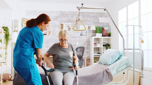 Alte behinderte dame, die mit hilfe von krücken im pflegeheim geht, während eine krankenschwester sich um sie kümmert