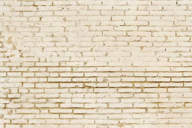 Alte beige backsteinmauerhintergrundbeschaffenheit