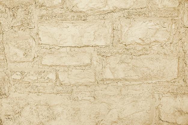 Alte beige steinwand-hintergrundbeschaffenheit