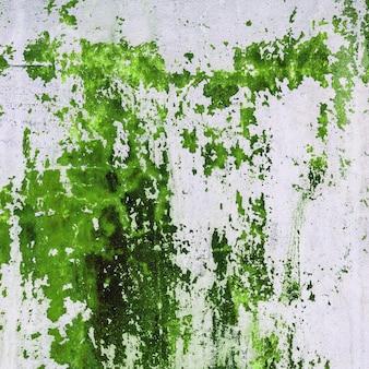 Alte betonmauer befleckt mit grüner farbe