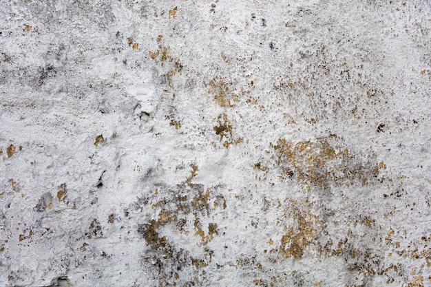 Alte betonmauer mit farbe, die vom hintergrund abblättert