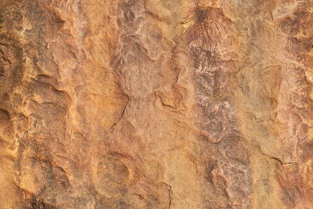 Alte braune felsstruktur in der natur mit schmutz und zerkratzt. abstrakter hintergrund.