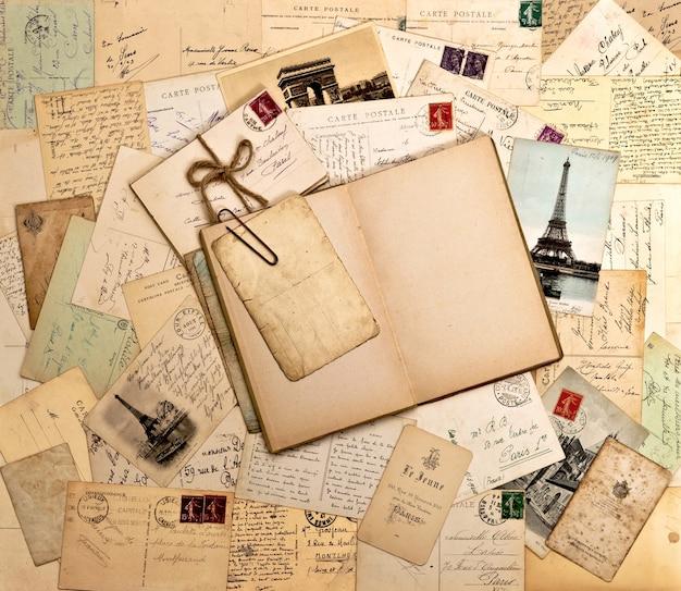 Alte briefe, französische postkarten und leeres offenes buch. nostalgischer vintage-hintergrund