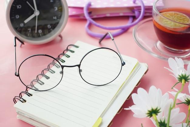 Alte brille auf einem notizblock auf rosa hintergrund,