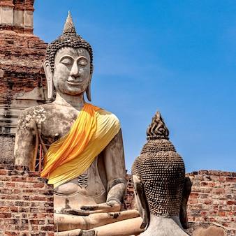 Alte buddha-statue bedeckt mit gelbem stoff
