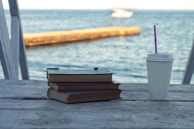 Alte bücher am strand mit kaffee zum mitnehmen meerwasser ist im hintergrund