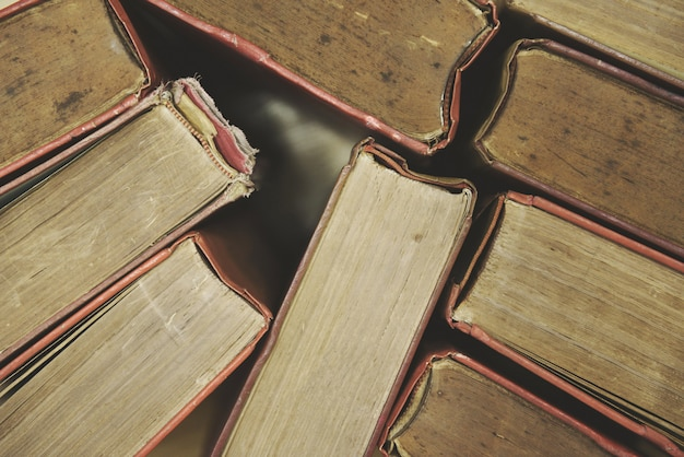 Alte bücher auf draufsichtbuchstapeln des bretterbodens im bibliotheksraum und im bildungshintergrund zurück zu schule