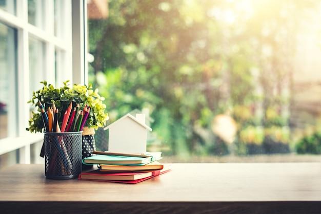 Alte bücher mit bleistift auf hölzerner tabelle mit unscharfem hintergrund am sonnenschein-tag