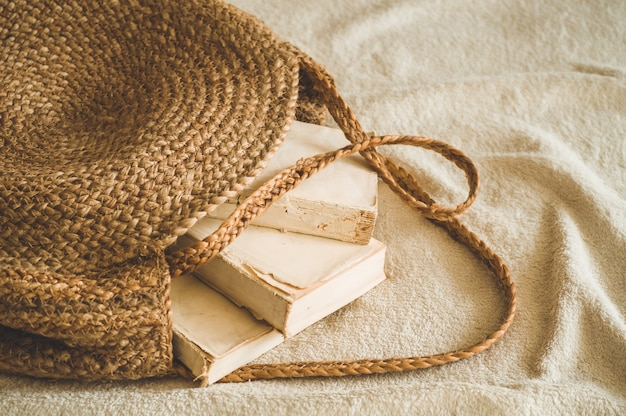 Alte bücher und vintage strohsack auf weißer warmer decke. bag stroh sommer frau. braune handgemachte naturtasche.